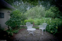 A private patio reprieve tucked next to a garden shed--a special feature that is hidden from the overall garden making it secretive and private for early morning coffee and good conversation.